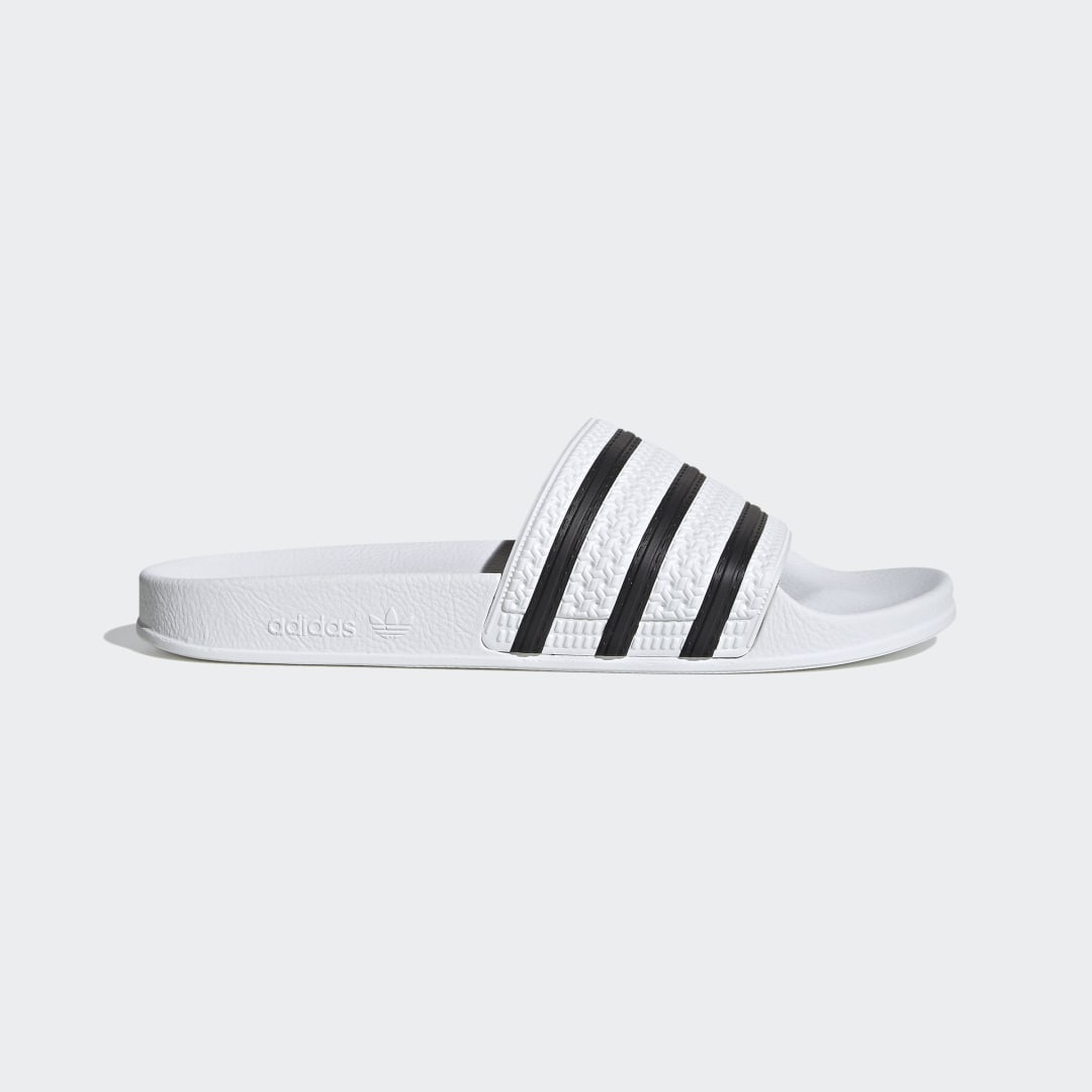adidas The Adilette debuted in 1972 as a poolside slide, and it\\\'s been a style mainstay of adidas ever since. These men\\\'s slides stay true to the authentic sporty look with a contoured footbed and 3-Stripes across the bandage upper.
