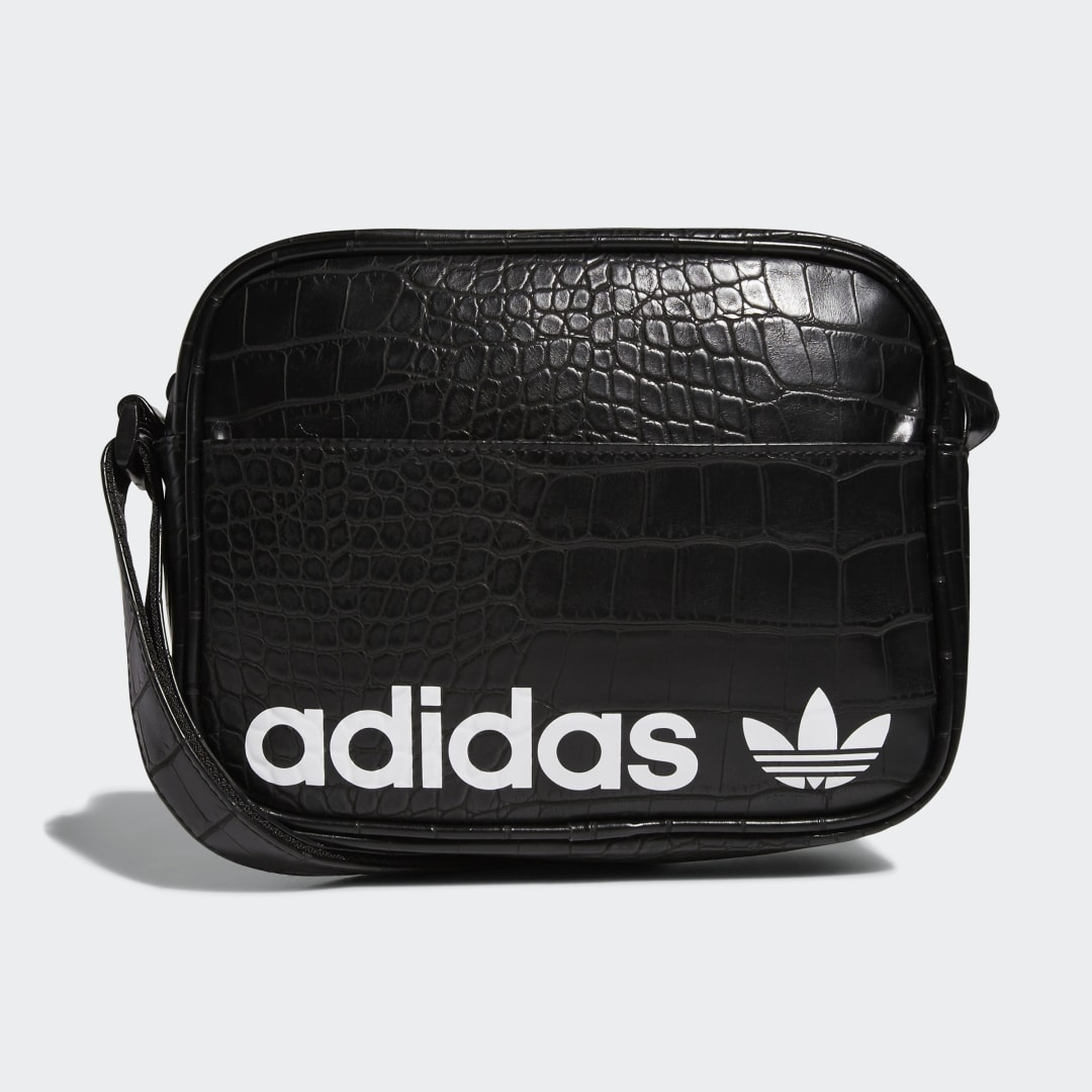 adidas Waiting at the airport gate just got a little more stylish. Small in size but big on elegance, this shoulder bag is a sized down version of the iconic adidas airliner bag. With its chic crocodile-inspired texture, it can go from the tarmac to dinner without looking out of place.